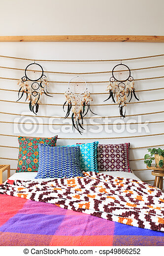 Bed with colorful sheets and dreamcatchers above stock images ...