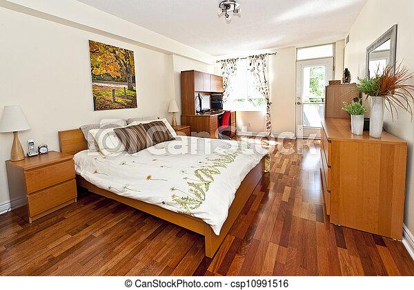 Bedroom interior with hardwood floor - csp10991516