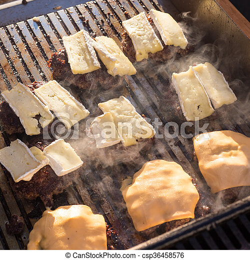 Beef burgers being grilled on barbecue. - csp36458576