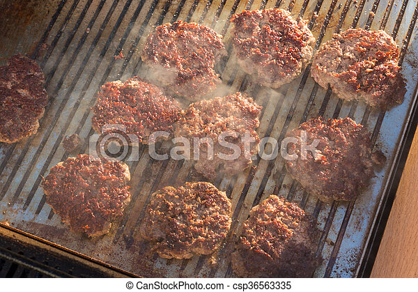Beef burgers being grilled on barbecue. - csp36563335
