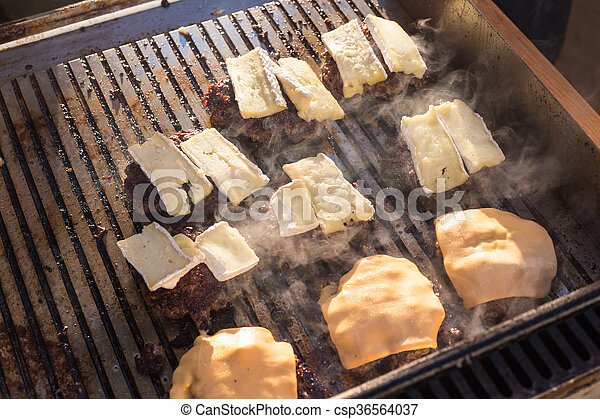 Beef burgers being grilled on barbecue. - csp36564037