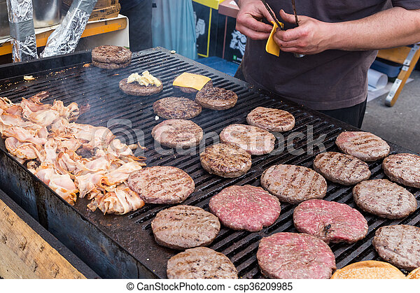 Beef burgers being grilled on food stall grill. - csp36209985