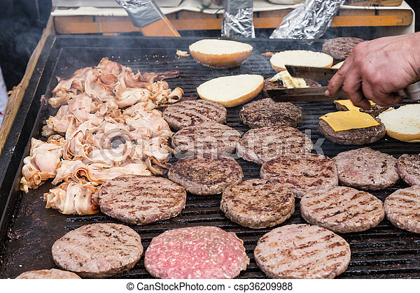 Beef burgers being grilled on food stall grill. - csp36209988