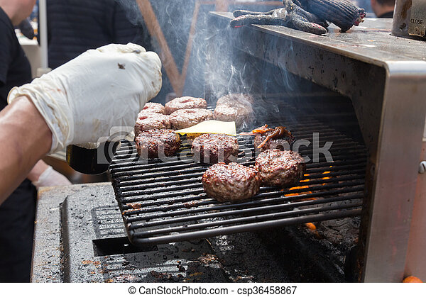 Beef burgers being grilled on food stall grill. - csp36458867
