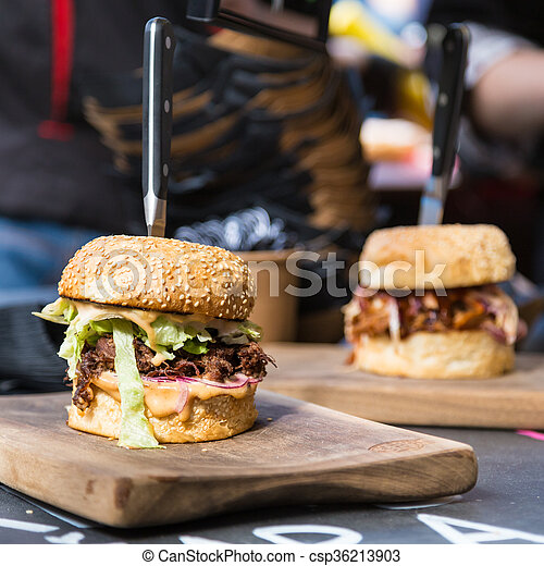Beef burgers being served on street food stall - csp36213903