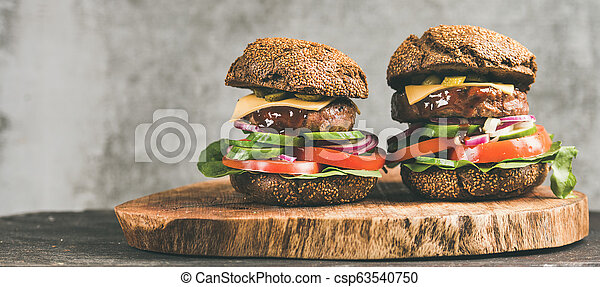 Beef meat cheeseburgers with barbeque sauce on board, wide composition - csp63540750