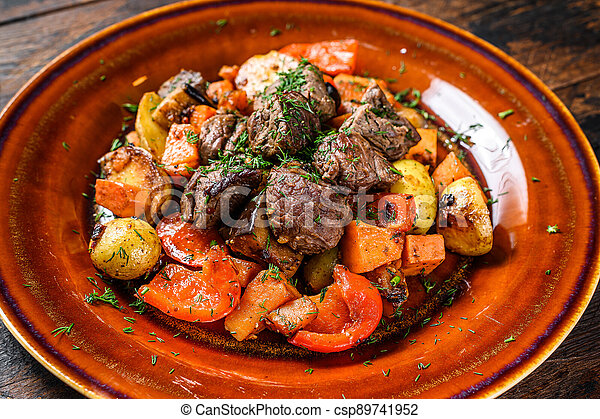 Beef meat stewed with vegetables on a plate. Dark wooden background. Top view - csp89741952