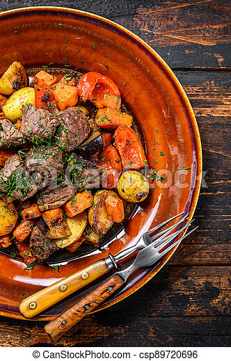 Beef meat stewed with vegetables on a plate. Dark wooden background. Top view - csp89720696