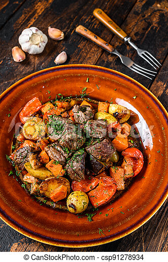 Beef meat stewed with vegetables on a plate. Dark wooden background. Top view - csp91278934