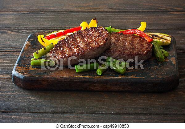 Beefsteak grilled with vegetables on a dark wood background - csp49910850
