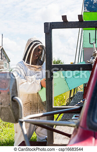 Beekeeper Carrying Honeycomb Crate By Truck - csp16683544