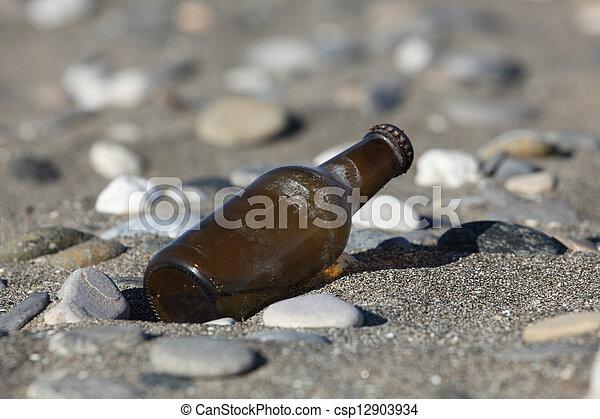 Beer bottle on the beach - csp12903934