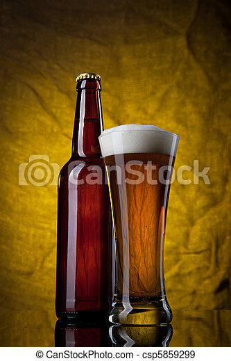 Beer in glass with bottle on yellow background - csp5859299