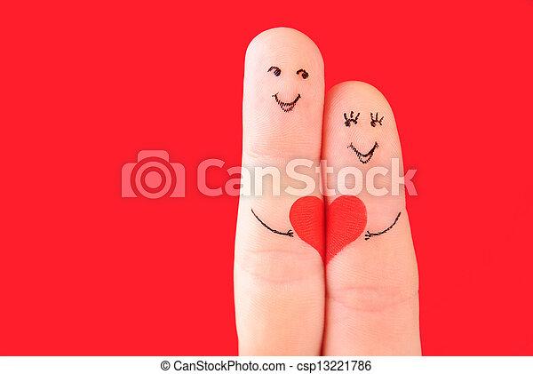 Familienkonzept - ein Mann und eine Frau halten das rote Herz fest, bemalt mit Fingern und isoliert auf rotem Hintergrund - csp13221786