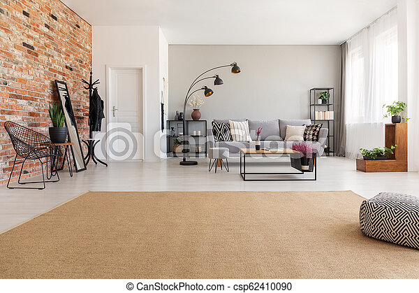 Beige carpet in modern living room interior with grey couch, industrial  black metal lamp, wooden coffee table and stylish furniture, real photo  with ...