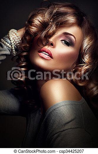 Chica sexy. Modelo de belleza posando sobre fondo oscuro - csp34425207
