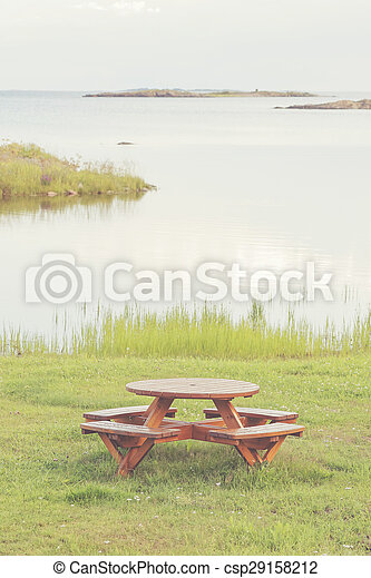 Bench at seashore with lush grass and view over the seascape - csp29158212