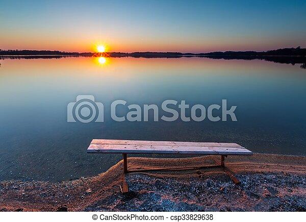 Bench on lake shore at sunset - csp33829638