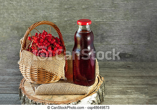 Berries of viburnum in a basket on a napkin next to the glass transparent bottle of juice. Rustic. Copy space - csp48649873