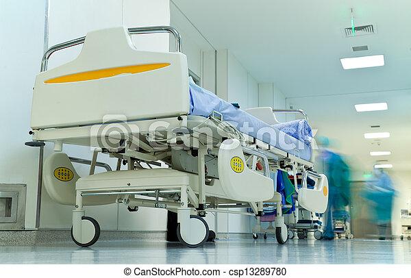 Leeres Bett im belebten Krankenhausgang, verschwommene Figuren mit medizinischer Uniform - csp13289780