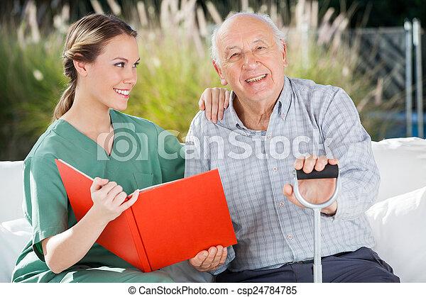 Glücklicher Senior-Mann, der von einer Krankenschwester sitzt - csp24784785