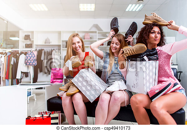 37185982f2 Best friends doing shopping together fooling around with new shoes laughing  putting them on head sitting in fashion store.