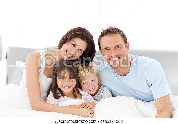 Portrait einer glücklichen Familie, die auf dem Bett sitzt - csp5174562