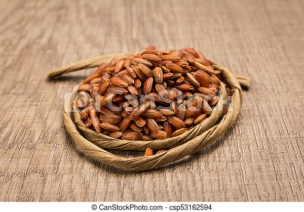 Bhutanese Red Rice seed. Paper rope around grain. Selective focus. - csp53162594