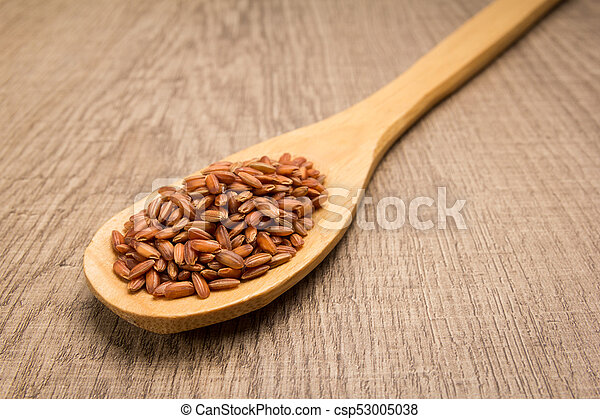 Bhutanese Red Rice seed. Spoon and grains over wooden table. - csp53005038