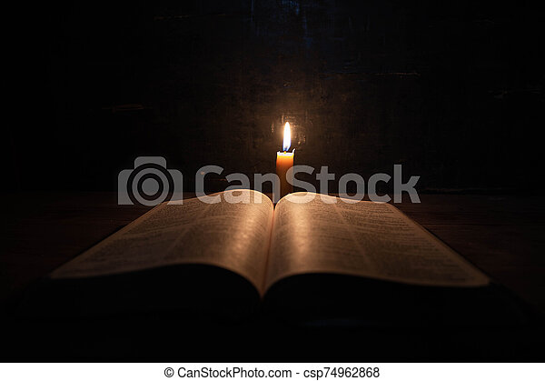 Bible and candle on a old oak wooden table. - csp74962868