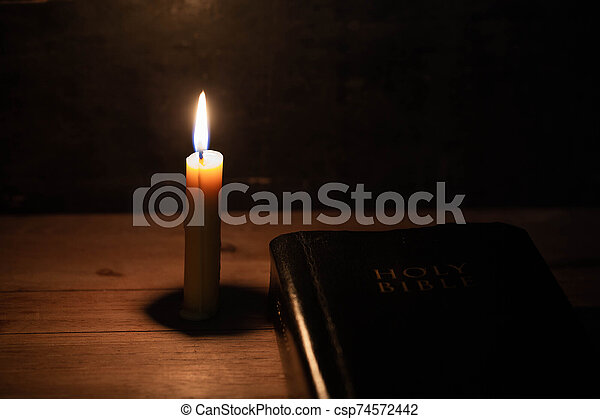 Bible and candle on a old oak wooden table. - csp74572442