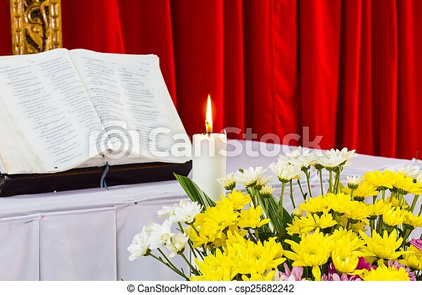 bible open on a table with candle - csp25682242