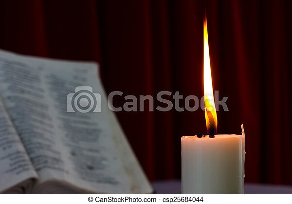 bible open on a table with candle - csp25684044