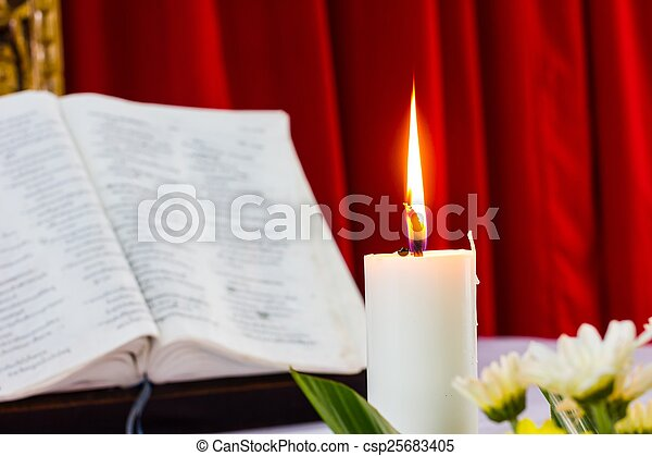 bible open on a table with candle - csp25683405