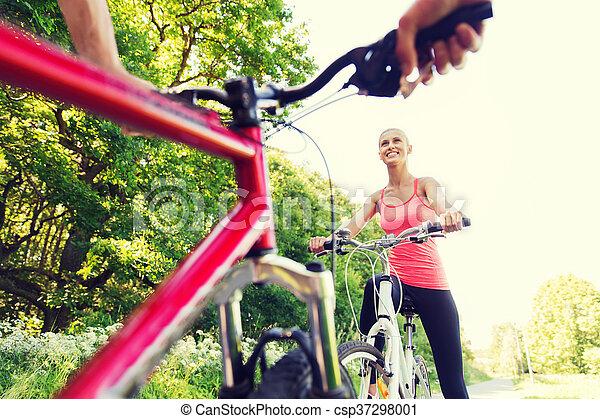 Cerca de una pareja feliz montando en bicicleta al aire libre - csp37298001