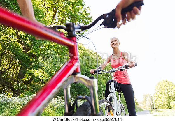 Cerca de una pareja feliz montando en bicicleta al aire libre - csp29327014