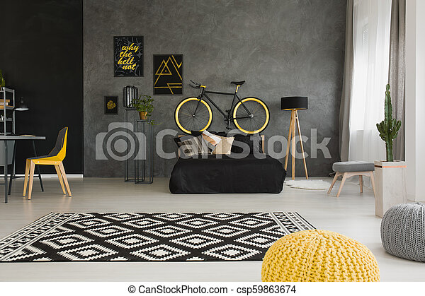 Swell Bicycle Above Black Bed In Dark Open Space Interior With Pouf And Yellow Chair At Desk Real Photo Pabps2019 Chair Design Images Pabps2019Com