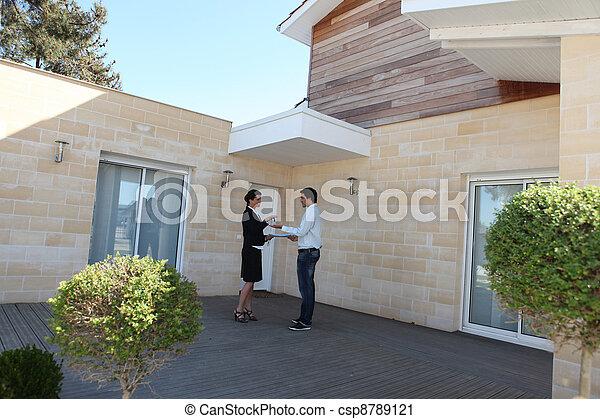 Mujer agente inmobiliario y joven comprando casa - csp8789121