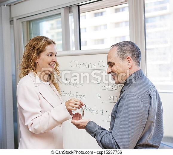 Agentes inmobiliarios dando llaves al cliente - csp15237756