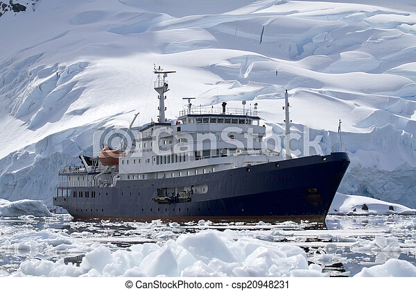 big blue tourist ship in Antarctic waters against the backdrop o - csp20948231