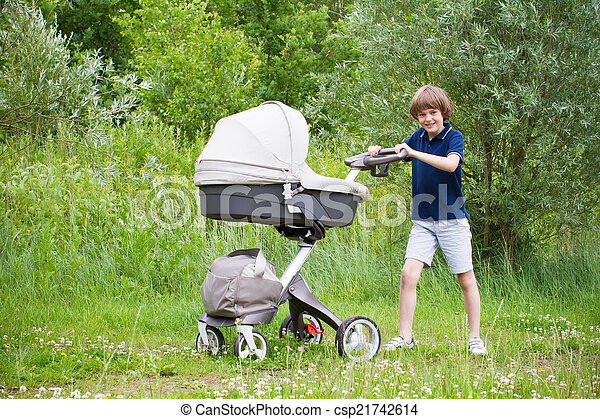 Big brother pushing a stroller in the park - csp21742614