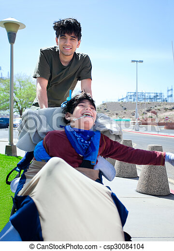 Big brother pushing happy disabled boy in wheelchair - csp30084104