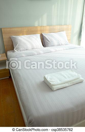 Big comfortable double bed in modern bedroom - csp38535762