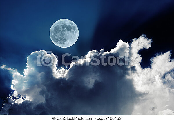 Big full moon in night sky with beautiful white clouds - csp57180452