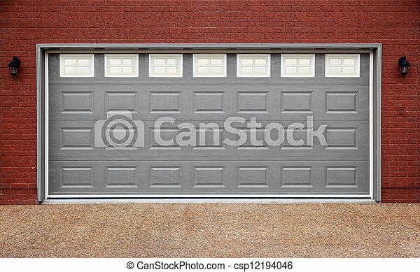 Big garage with gray doors, brick wall and asphalt driveway - csp12194046