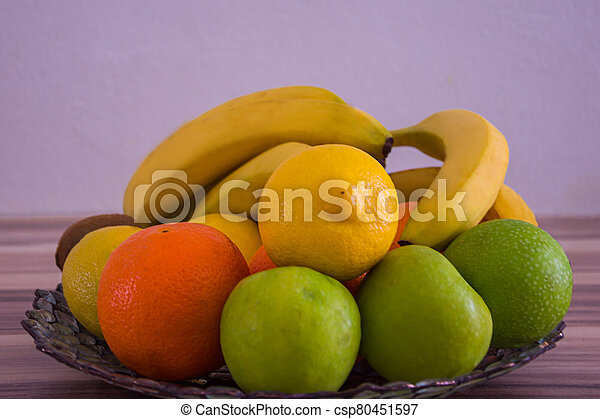 Big glass bowl full with fruits on a wooden table - csp80451597