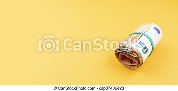 big money roll of euro banknotes with rubber band against orange background - csp87406423
