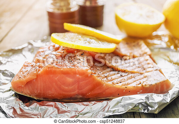 Big pink piece of salmon with herbs and lemon rests on a shiny piece of foil. - csp51248837