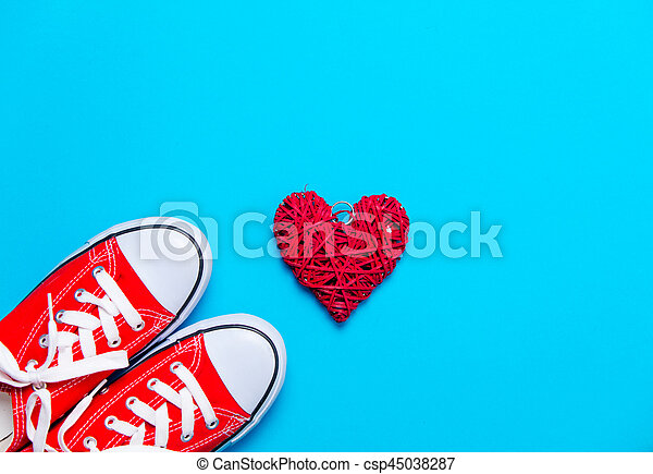 big red gumshoes and beautiful heart shaped toy on the wonderful blue background - csp45038287