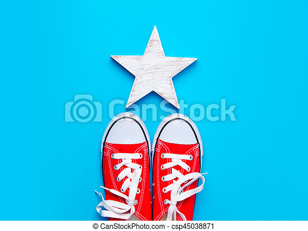 big red gumshoes and beautiful star shaped toy on the wonderful blue background - csp45038871